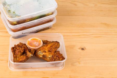 Photo pour Convenient but unhealthy disposable plastic lunch boxes with take away meal on wooden table - image libre de droit