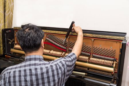 Photo for Technician cum musician tuning an upright piano using lever and tools - Royalty Free Image