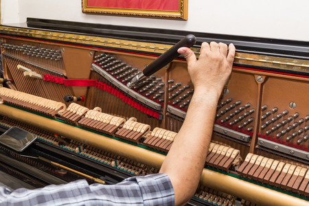 Photo for Closeup on hand tuning an upright piano using lever and tools - Royalty Free Image