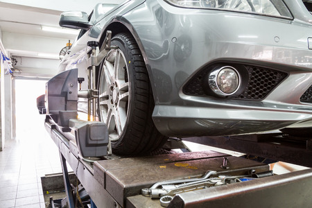 Photo pour Closeup of tire clamped with aligner undergoing auto wheel alignment in garage - image libre de droit