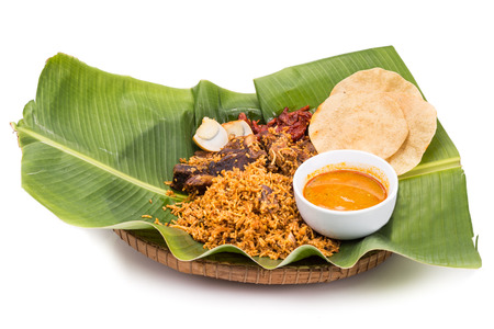 Aromatic delicious nasi briyani meal with mutton and dhal on banana leaf and rattan plate, a popular Indian cuisine