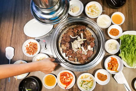 Photo pour Person barbecue beef on bbq pit during korean meal set in restaurant - image libre de droit