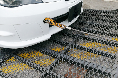 Photo pour Broken down auto vehicle car towed onto flatbed tow truck with hook and chain - image libre de droit