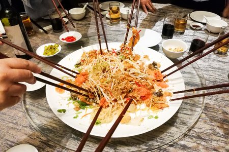 Photo pour People tossing yee sang or yusheng during Chinese New Year , traditional practice in Malaysia and Singapore for luck and prosperity - image libre de droit