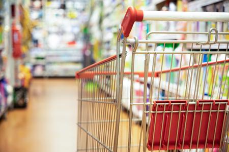 Photo pour Shopping trolley cart against modern supermarket aisle blurred background - image libre de droit