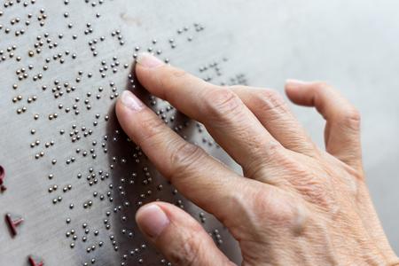 Photo pour Finger reading braille tactile on public park message board in Hong Kong - image libre de droit