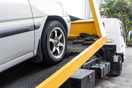Foto de Broken down car being towed onto flatbed tow truck with cable for repair at workshop garage - Imagen libre de derechos