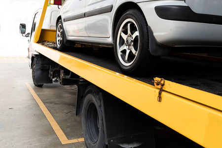 Photo pour Broken down car on flatbed tow truck being transported to garage workshop for repair - image libre de droit