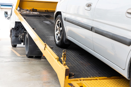 Photo pour Broken down car being towed onto flatbed tow truck with cable for repair at workshop garage - image libre de droit
