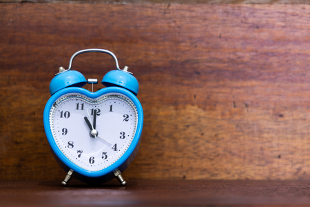 Photo for Heart shaped alarm clock on wooden background. Time is Eleven O Clock - Royalty Free Image