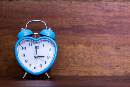 Photo pour Heart shaped alarm clock on wooden background. Time is Three O Clock - image libre de droit