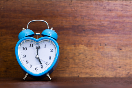 Photo pour Heart shaped alarm clock on wooden background. Time is Five O Clock - image libre de droit