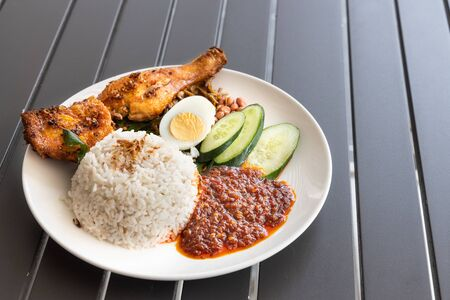 Photo for Nasi lemak with spice fried chicken, egg, anchovies, peanuts and sambal, Malaysia popular food - Royalty Free Image