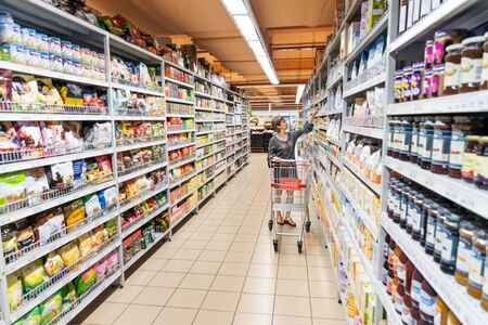 Photo pour Series of Asian woman shopping groceries in modern supermarket with shopping cart selecting products - image libre de droit
