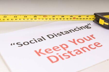 Photo pour Social Distancing concept with measuring tape focused on 1 meter mark against Keep Your Distance placard - image libre de droit