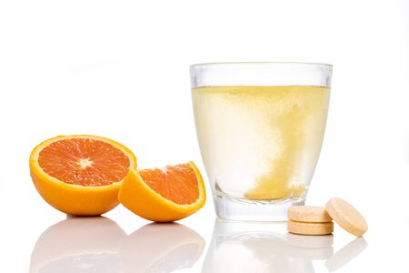 Photo pour Series of orange flavored vitamin c effervescent tablet dropped and dissolve in glass of water on white background - image libre de droit