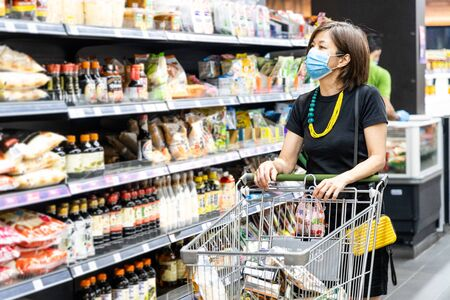 Foto für Asian woman shopping groceries in supermarket with protective face mask as new normal requirement in Malaysia - Lizenzfreies Bild