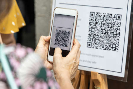 Foto de Modified inactive QR Code used.  Person scanning QR code with smartphone to register details before enter outlet to comply with contact tracing rule to manage covid-19 spread. - Imagen libre de derechos