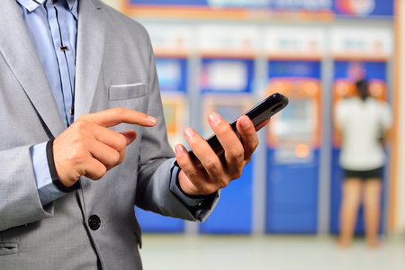 Businesssman using Mobile Banking Application on Smartphone near ATM or Automatic Teller Machine System as Tele-Banking or shopping online concept