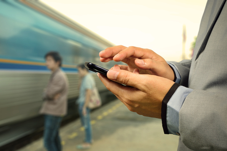 Business Man use Mobile Phone in Railway Station with Running Train