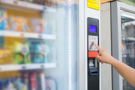 Photo pour Female Hand Push Button to make Transaction Code or Number on Modern Automatic Vending Machine with Digital Display.  This Machine Can be operated with Both coin and Banknote. - image libre de droit