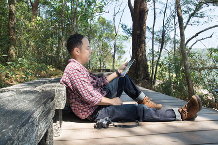 Male Hand use Digital Mobile Wireless Tablet PC to read e-mail or E-book and Travel information map while travel Trekking in forest National Park as Internet Technology for Trekker Hiker Telecommunication Concept.