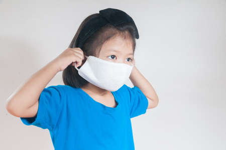 Asian child Girl or kids in blue Shirt wearing cloth mask to protect Covid 19 virus infection as medical safety prevention concept against white background.
