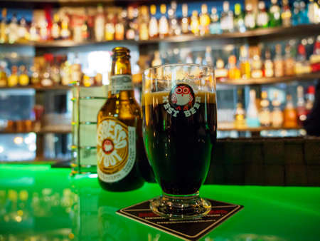 Photo pour TOKYO, JAPAN - MARCH 31, 2019: Wide closeup detail of a glass of Hitachino Nest espresso stout beer nest to a bottle on a bar counter, liqour on the shelves. Travel and party. - image libre de droit