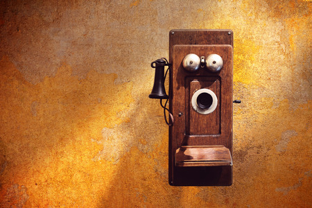 Photo for Antique Wall Telephones on dirty yellow wall - Royalty Free Image