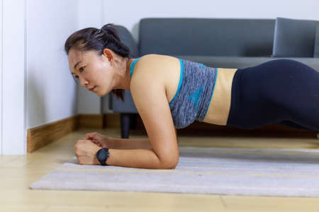 Foto für Portrait beautiful adult (40 years old) Asian woman doing Home Workout in Sports Clothing with Stretching Exercise in the room white background. People's body and health care lifestyle concepts. - Lizenzfreies Bild