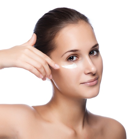 Photo pour Portrait of beautiful woman applying cream on face - isolated on white  - image libre de droit