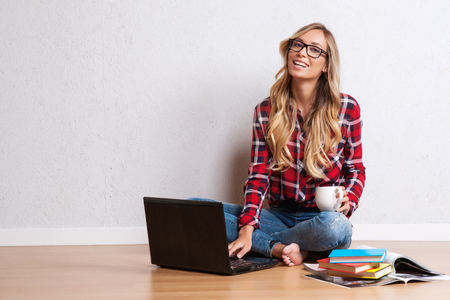 Photo for Young creative woman sitting in the floor with laptop./ Casual blogger woman - Royalty Free Image
