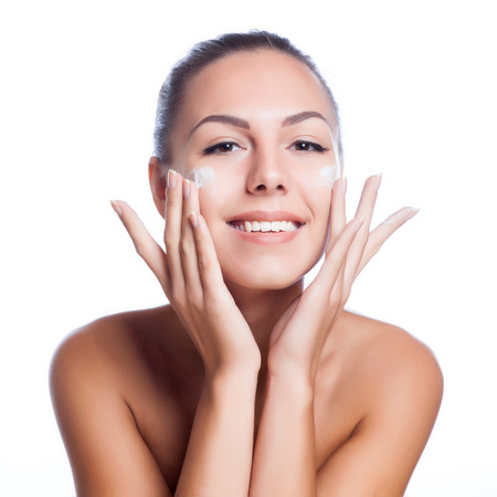 Photo pour beautiful model applying cosmetic cream treatment on her face on white - image libre de droit