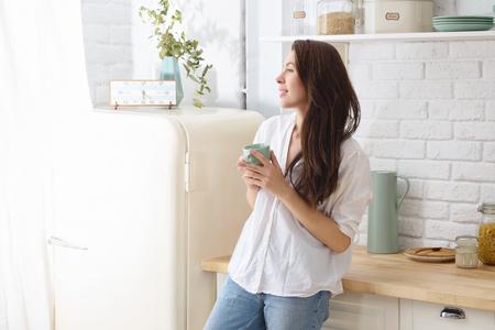 Foto de Young happy woman drinking coffee on the kitchen in the morning. - Imagen libre de derechos