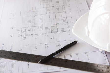 Photo pour Close-up of blueprints with sketches of projects, pen, ruler and white helmet. - image libre de droit