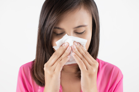 Flu cold or allergy symptom. Sick woman girl sneezing in tissue on blue. Health care.