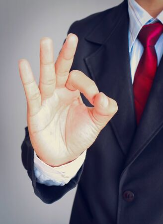 Businessman hand showing sign OK on gray background.