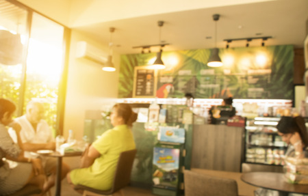 Blurred image of unidentified people relax at the coffee shop