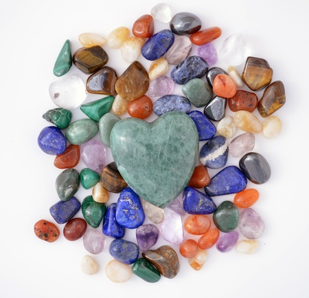 Green quartz heart on multicoloured pebbles of semiprecious stones