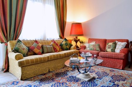 Photo pour Elegant living room with classic looking sofa, colorful curtains, lamp and glass table - image libre de droit