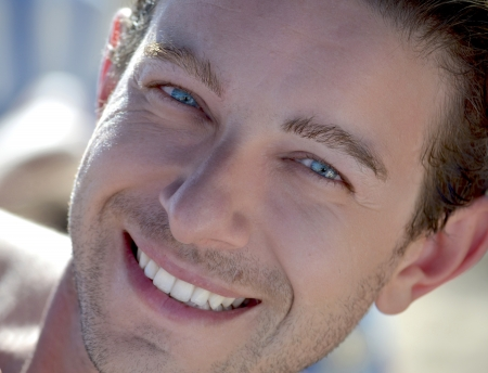 Head shot of blue eyed attractive male model smiling