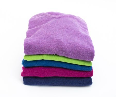 Stack of colorful wool or cashmere sweaters isolated on white