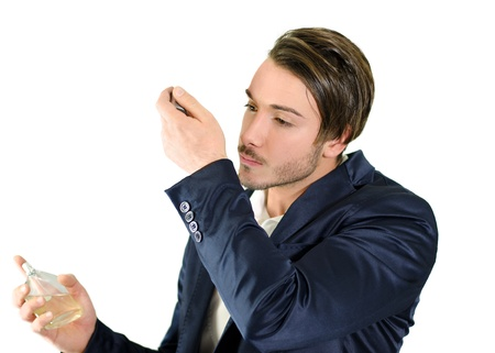 Attractive young man spraying and smelling fragrance or cologne, isolated
