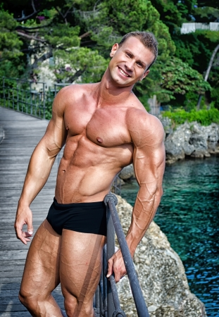 Smiling young bodybuilder standing with sea or ocean behind showing muscular torso, pecs, arms and abs