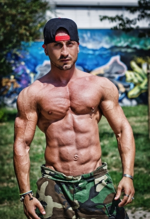 Attractive bodybuilder shirtless with baseball hat showing torso muscles, abs, pecs and arms