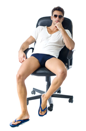 Attractive young man in t-shirt, with naked legs on office chair, isolated on white background