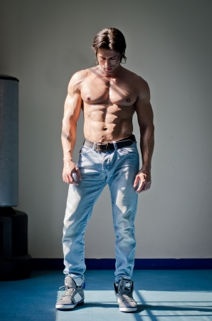 Full figure shot of muscular man shirtless in jeans, looking down
