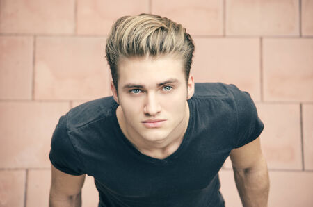 Attractive blond young man shot from above, looking up towards camera