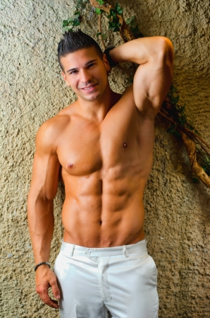 Muscular young latino man shirtless in white pants leaning on wall, smiling and looking at camera