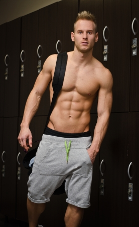 Shirtless muscular young male athlete in gym dressing room, with backpack on shoulder